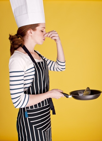 A young female cook holding her nose to block out the smell of fresh raw fish   Stock Photo