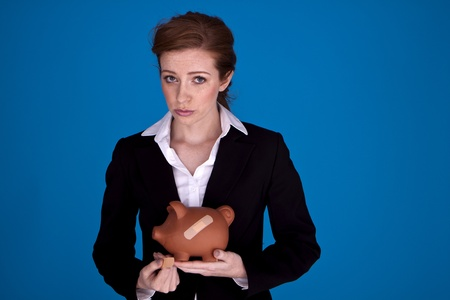 Young attractive businesswoman holding a piggybank with plasters on it as a money recovery concept. photo