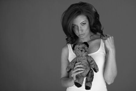 Beautiful young woman holding her small toy bear  photo