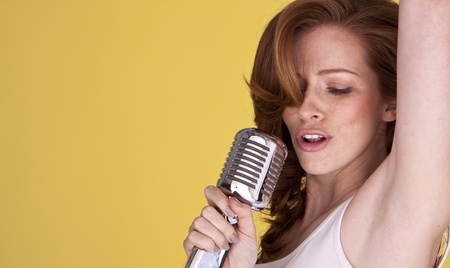 Retro redhead female singer with microphone singing her heart out  Stock Photo - 12411398