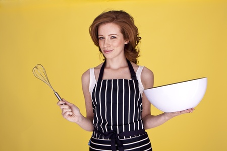 An attractive housewife is preparing a mixture for baking.