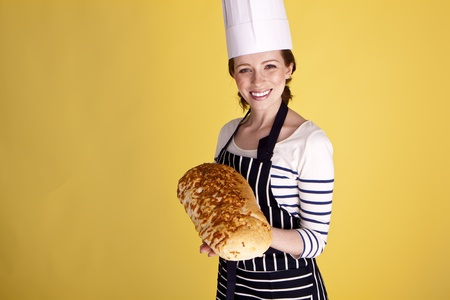 A beautiful female baker showing of a freshly baked loaf of bread.  photo