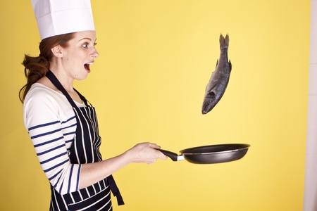 A young attractive female chef flipping a fish in a pan.  Stock Photo