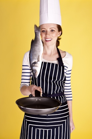 A young attractive female chef flipping a fish in a pan.  Stockfoto