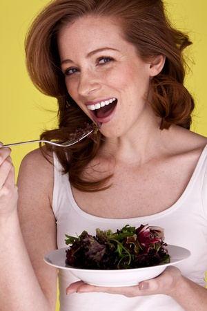 A young attractive woman holding a plate and eating a fresh garden salad. Stock Photo - 12100555