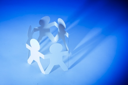 Paper men as a team linked together to illustrate a partnership concept Stock Photo - 12411416