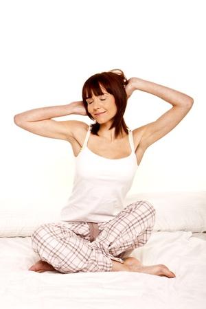 Eine junge Frau streckt, als sie aufwacht aus einem guten Schlaf Standard-Bild - 12717641
