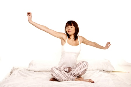 A young woman stretches as she wakes up from a good nights sleep