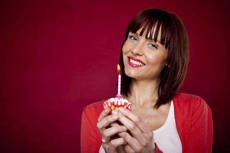 A beautiful woman is holding a cupcake with one burning candle