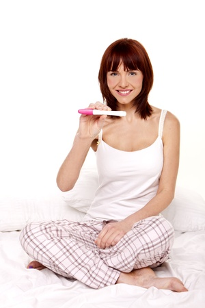 A young woman sitting on her bed holding a pregnancy test stick