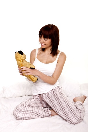 A young woman wearing pyjamas holding her teddy bear in bed   photo