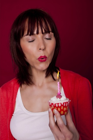 A beautiful woman is blowing out a candle on a cupcake and making a wish for her birthday   photo