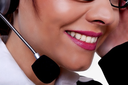 A close-up image of a beautiful woman with a friendly smile talking on a phone at a call centre. photo