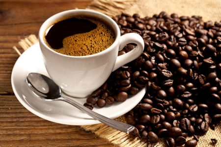 Freshly made coffee in a white cup surrounded by coffee beans on a wooden table   Standard-Bild
