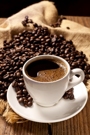 Freshly made coffee in a white cup surrounded by coffee beans on a wooden table Stock Photo - 13006825