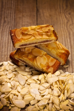 Two delicious almond sponge slices on a wooden table.  photo