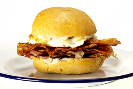A delicious bacon and egg bun on a white background.  photo