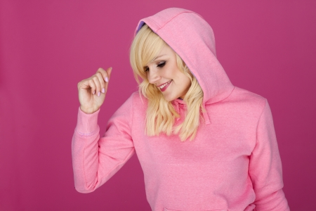 Happy woman wearing a pink sports hoodie on a pink background