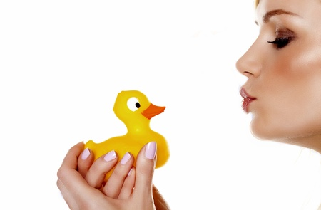 A beautiful woman pouting her lips to kiss her toy rubber duck   Stock Photo