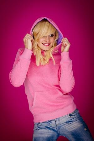 Gelukkige vrouw het dragen van een roze sport hoodie op een roze achtergrond Stockfoto