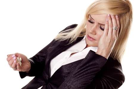 painkillers: A stressful businesswoman with a migraine holding painkillers   Stock Photo