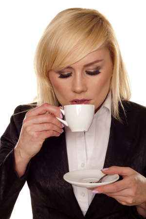 A beautiful blond businesswoman drinking coffee from a small white cup   photo