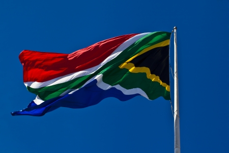 The South-African flag wavering in the wind against a blue sky  photo
