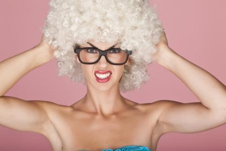 Femme ludique et amusant porter une perruque fris�e sur un fond rose photo