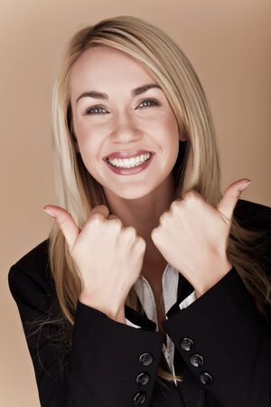 You blond businesswoman holding her thumbs up  photo
