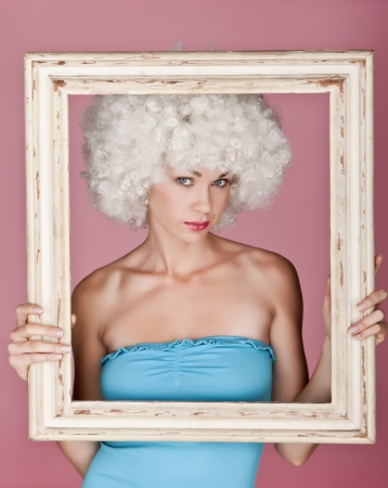 Playful and funny woman wearing a curly wig on a pink background