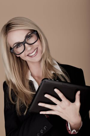 A attractive blond businesswoman holding a black tablet computer  photo