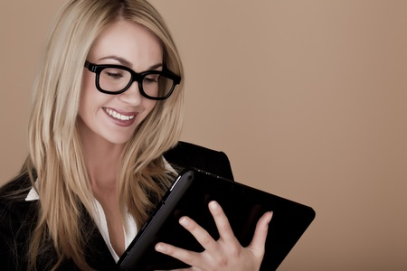A attractive blond businesswoman holding a black tablet computer