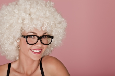 Playful and funny woman wearing a curly wig on a pink background  photo