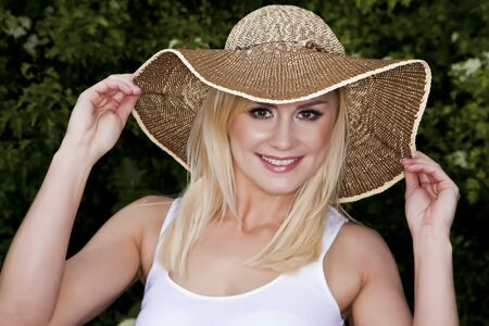 An attractive blond woman wearing a hat against a leafy green background  photo