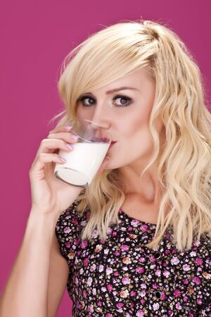 An attractive blond woman drinking a glass of milk  photo