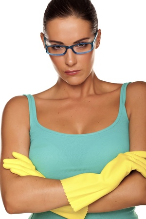 An attractive young woman with brunet hair wearing a blue vest top and yellow rubber cleaning gloves on a white background   photo