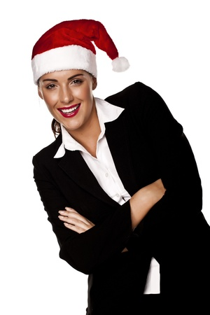 A beautiful young businesswoman wearing a Santa hat on a white background   photo