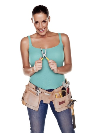 A woman wearing a DIY tool belt full of a variety of useful tools on a white background  Standard-Bild