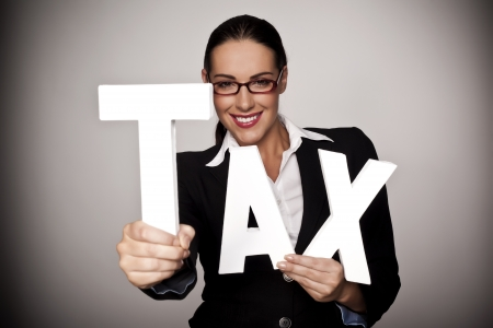 A businesswoman holding letters to spell out tax as a pay your tax concept   Stockfoto
