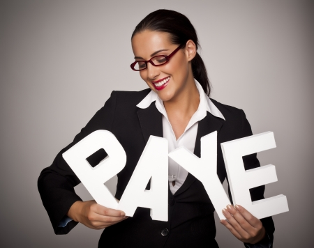 Income tax concept with a beautiful businesswoman holding letters spelling out PAYE that stands for pay as you earn  Stock Photo