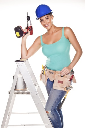 A woman wearing a DIY tool belt full of a variety of useful tools on a white background. photo