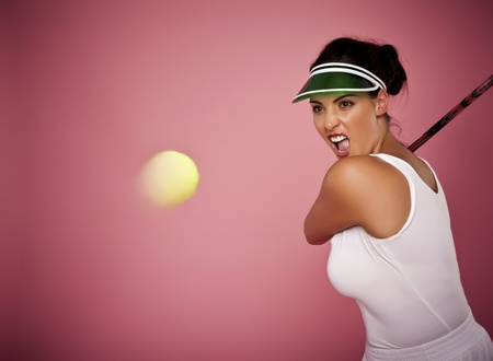 A beautiful woman enjoying the great game of tennis on a pink background. Stock Photo - 16249965