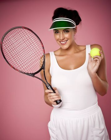 A beautiful woman enjoying the great game of tennis on a pink background. photo
