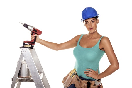 A woman wearing a DIY tool belt full of a variety of useful tools on a white background  Stockfoto