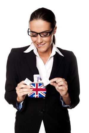 A businesswoman holding British twenty pond notes in a small perch as a savings concept  photo