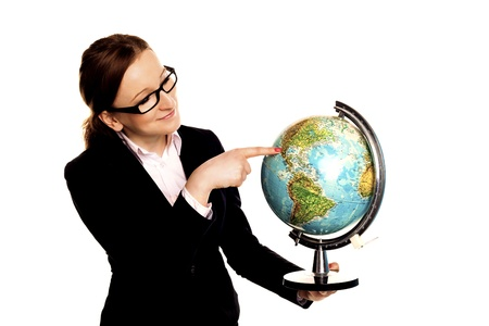 A beautiful businesswoman holding and pointing to a world globe as a business concept for world trade   photo