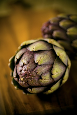 Two organic artichokes on a wooden board. Stock Photo