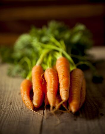 A bunch of organic carrots on a wooden table with a shallow depth of field. photo