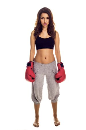 A female kick boxer wearing red gloves with a muted look on her face  photo