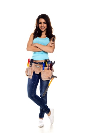 A woman wearing a DIY tool belt full of a variety of useful tools on a white background